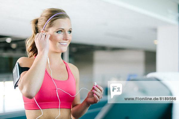 Junge Frau mit Smartphone-Armband und Ohrstöpseln