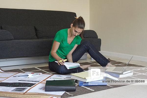 Mittlere erwachsene Frau auf dem Boden sitzend studierend