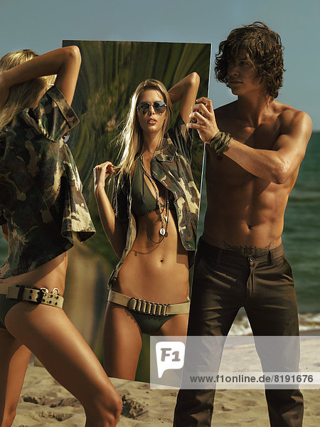Frau in einem Outfit im Militär-Stil am Strand  Reflexion in einem Spiegel  der von einem Mann gehalten wird