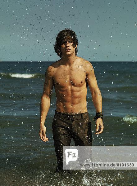 Mann mit nackter Brust und langer Hose  im Meer stehend