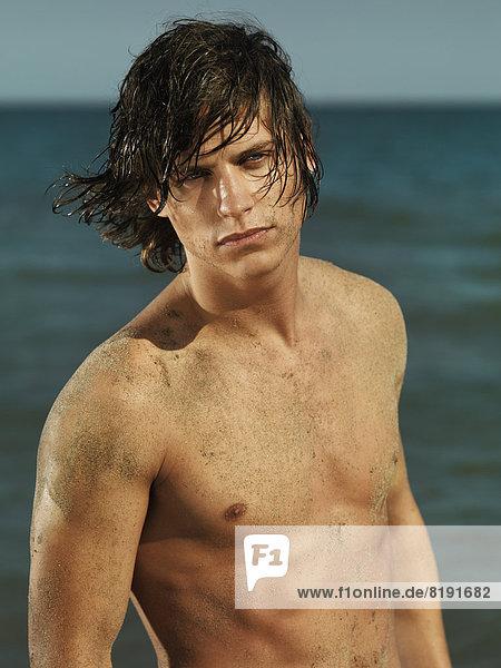 Mann mit nackter Brust und nassen Haaren  am Meer