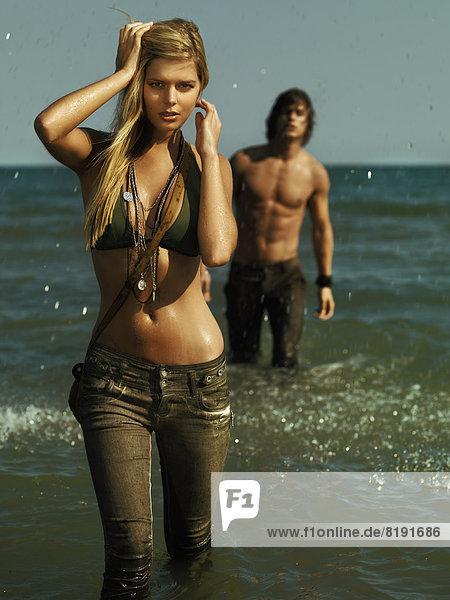 Frau im Bikini-Oberteil und langer Hose im Meer  Mann steht hinter ihr
