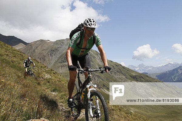 Mountain bikers riding downhill at the Passo della Vallaccia pass