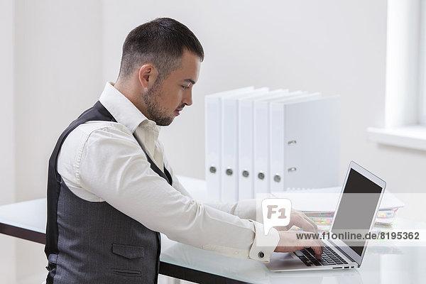 benutzen  Schreibtisch  Notebook  Geschäftsmann  jung
