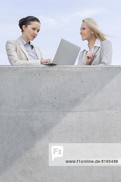 niedrig  stehend  benutzen  Geschäftsfrau  Notebook  Himmel  Ansicht  Flachwinkelansicht  Terrasse  Kollege  Winkel
