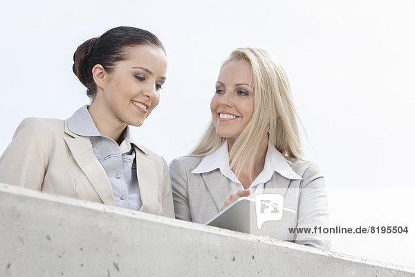 niedrig  stehend  benutzen  Geschäftsfrau  lächeln  Himmel  Ansicht  Flachwinkelansicht  Tablet PC  Terrasse  Winkel