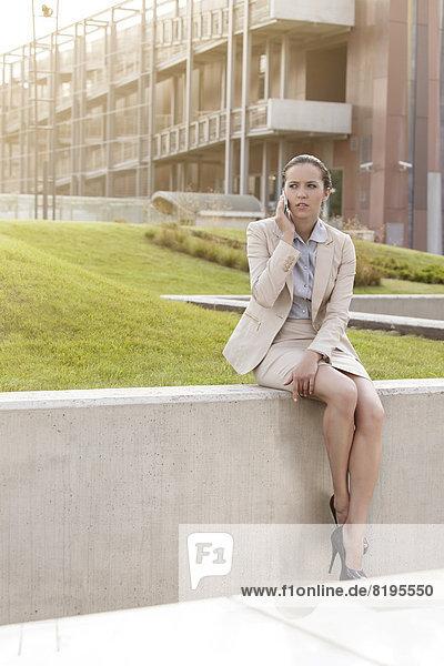 sitzend  benutzen  Geschäftsfrau  Wand  Gebäude  Telefon  Büro  jung  Länge  Handy  voll