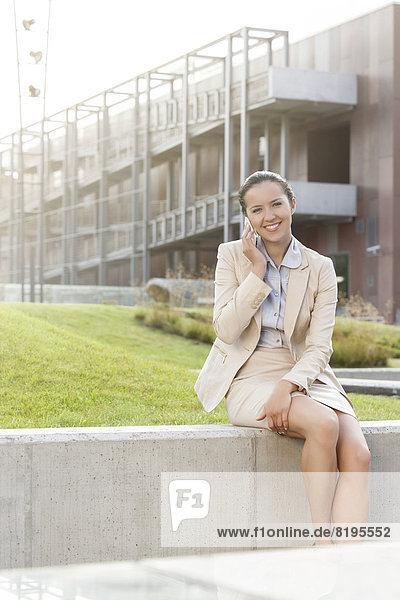 sitzend  benutzen  Geschäftsfrau  Handy  Fröhlichkeit  Wand  Gebäude  Telefon  Büro  jung