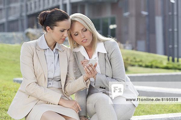 sitzend  Zusammenhalt  benutzen  Geschäftsfrau  Handy  Gebäude  Telefon  Büro  jung