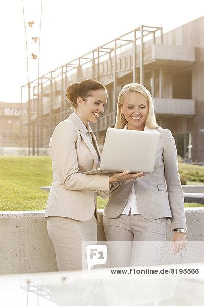 stehend  Zusammenhalt  benutzen  Geschäftsfrau  Fröhlichkeit  Notebook  Gebäude  jung