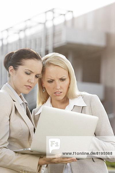 stehend  Geschäftsfrau  Notebook  ernst  arbeiten  Gebäude  Büro  jung