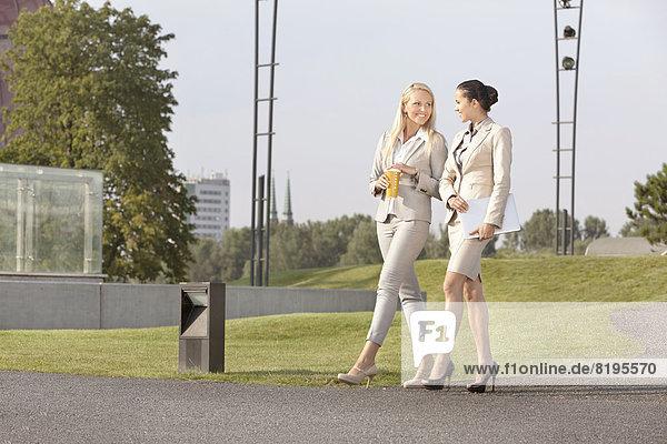 Full length of happy businesswomen walking together on street