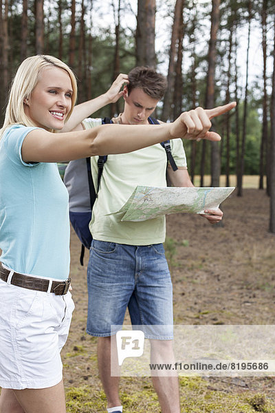 Young woman pointing away with confused man holding map in forest