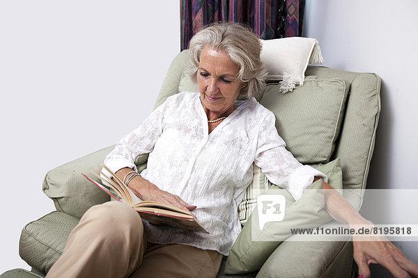 Interior zu Hause Senior Senioren Frau Entspannung Buch Sessel Taschenbuch vorlesen