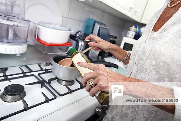Anschnitt  Senior  Senioren  Frau  Fotografie  Küche  Olive  Kochtopf  hinzufügen  Tresen  Öl