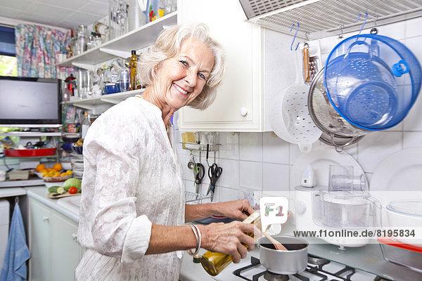 Senior  Senioren  Portrait  Frau  eingießen  einschenken  Küche  Olive  Kochtopf  Öl