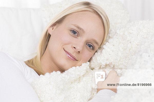 Porträt einer jungen Frau auf der Couch liegend  lächelnd