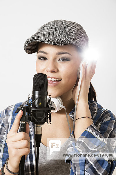 Porträt einer jungen Frau  die im Mikrofon singt  lächelnd