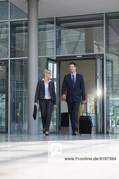 Geschäftsmann und Geschäftsfrau zu Fuß mit Aktentasche am Terminal
