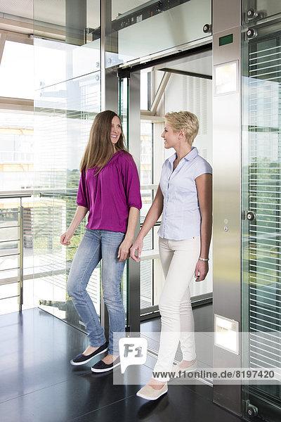 Geschäftsfrau im Aufzug  lächelnd