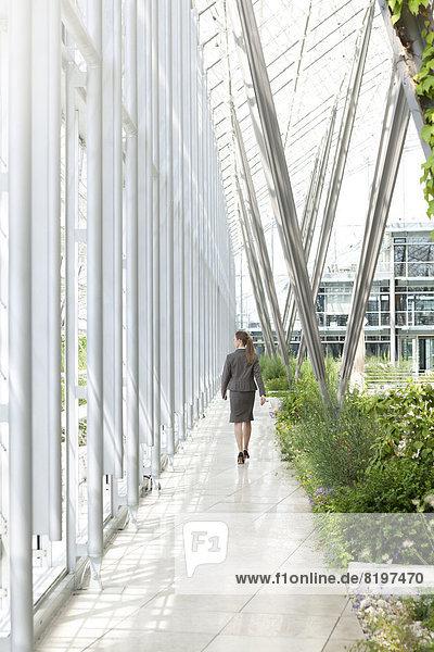 Businesswoman walking in modern courtyard