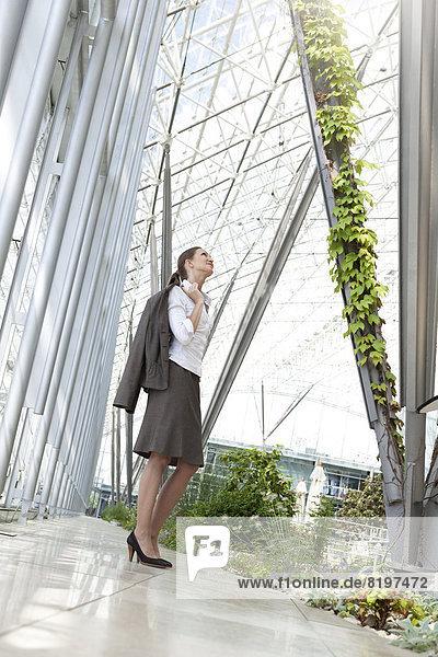 Geschäftsfrau steht im modernen Innenhof