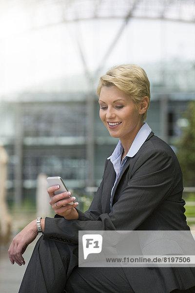 Geschäftsfrau mit Smartphone  lächelnd