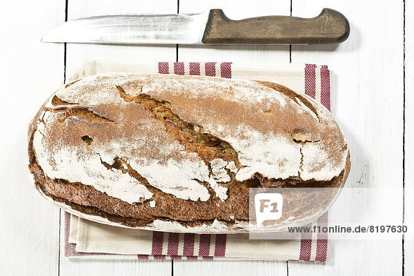 baked bread with napkin and knife on wooden table  close up