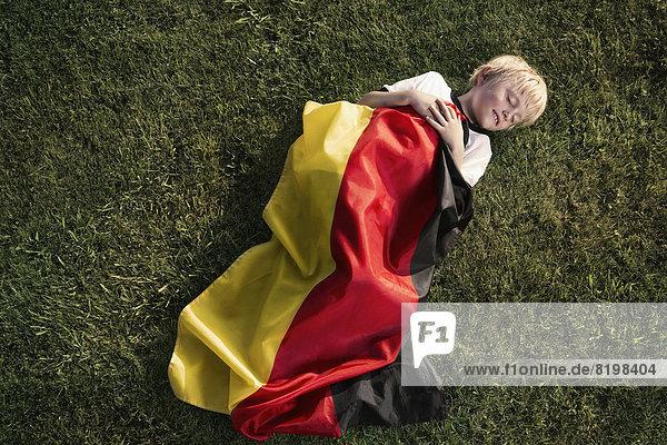 Deutschland,  Köln,  Junger Fußballfan schläft in deutscher Fahne