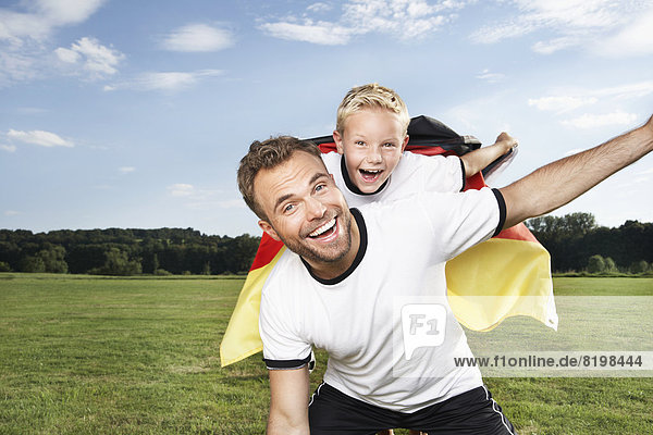 Germany  Cologne  Father and son cheering in football outfit