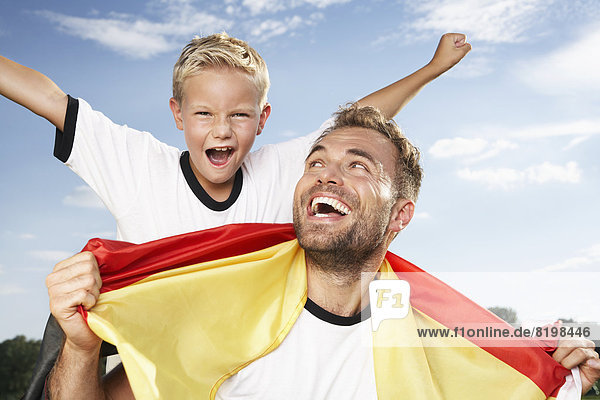 Deutschland,  Köln,  Vater und Sohn jubeln im Fußball-Outfit