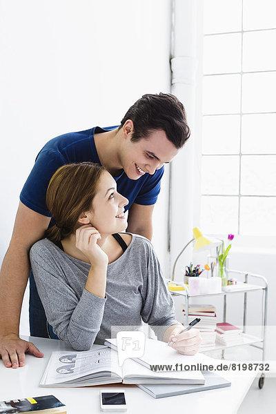 Deutschland  Bayern  München  Junges Paar studierend  lächelnd