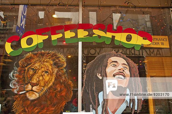 Ein rauchender Löwe und Bob Marley  gemalt auf das Fenster von einem Coffee-Shop