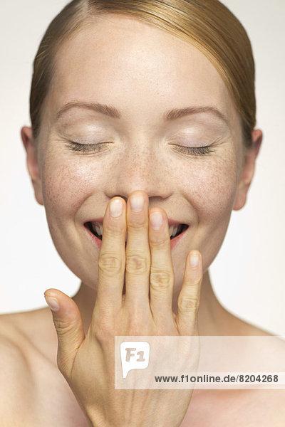 Junge Frau lächelnd  den Mund mit der Hand bedeckend