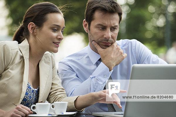 Geschäftspartner  die an einem Projekt mit Hilfe eines Laptops zusammenarbeiten