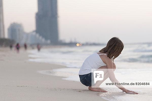 Mädchen kauernd am Strand mit Wasser spielen  Seitenansicht