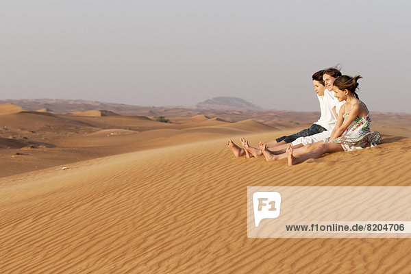 Kinder  die zusammen auf einer Sanddüne sitzen und die Aussicht betrachten