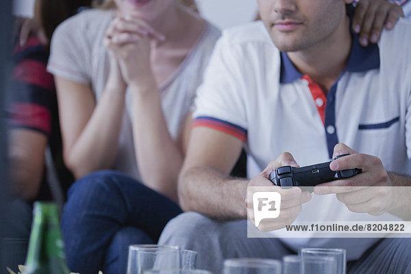 Junger Mann spielt Videospiel  während ein Freund zuschaut.