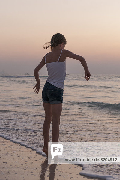 Mädchen beim Spielen am Strand  Rückansicht