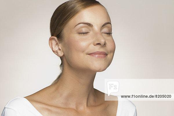 Junge Frau lächelt mit geschlossenen Augen