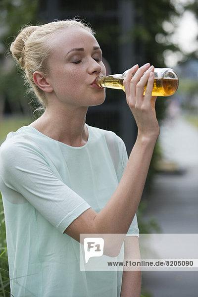 Frau trinkt Bier beim geselligen Beisammensein