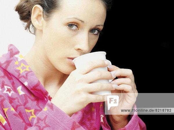 Frau im Morgenmantel trinkt Kaffee