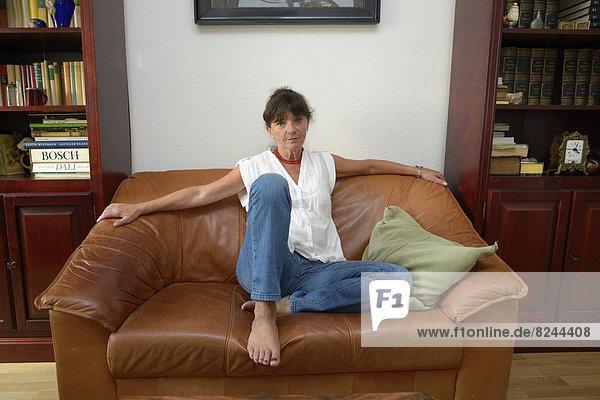 Frau  Mitte 60  sitzt auf Sofa