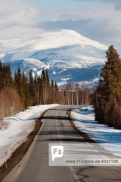 Road gehen durch verschneite Landschaft
