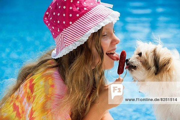 Girl and puppy sharing a popsicle.