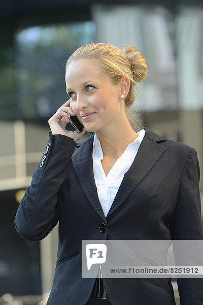 Junge blonde Geschäftsfrau mit Handy im Freien