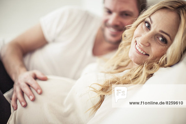 Porträt einer glücklichen schwangeren Frau mit einem im Bett liegenden Mann