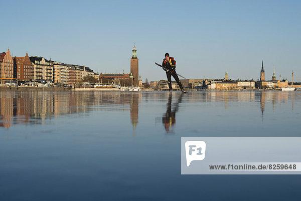Mann beim Eislaufen auf dem zugefrorenen See
