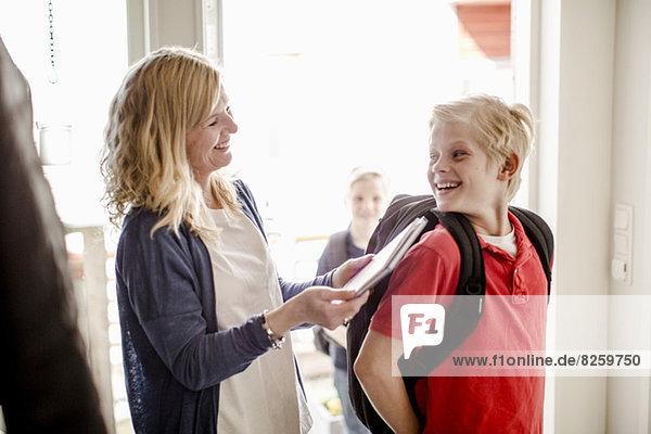 Fröhlicher Junge mit Rucksack und Blick auf Mutter mit Buch