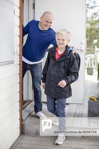 Portrait of happy boy leaving for school while father looking at him